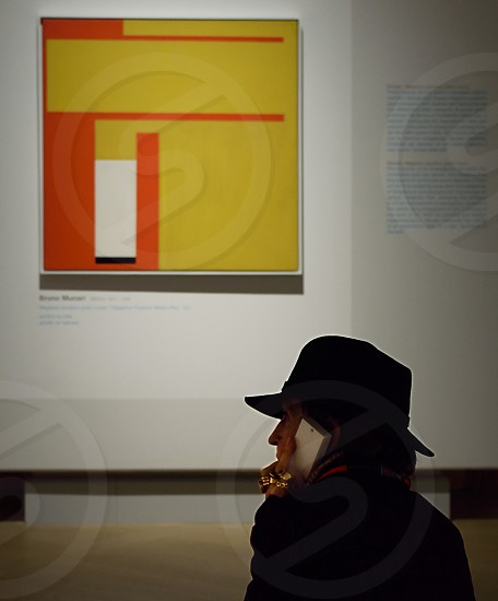 woman with hat talking at the phone during an exibition photo