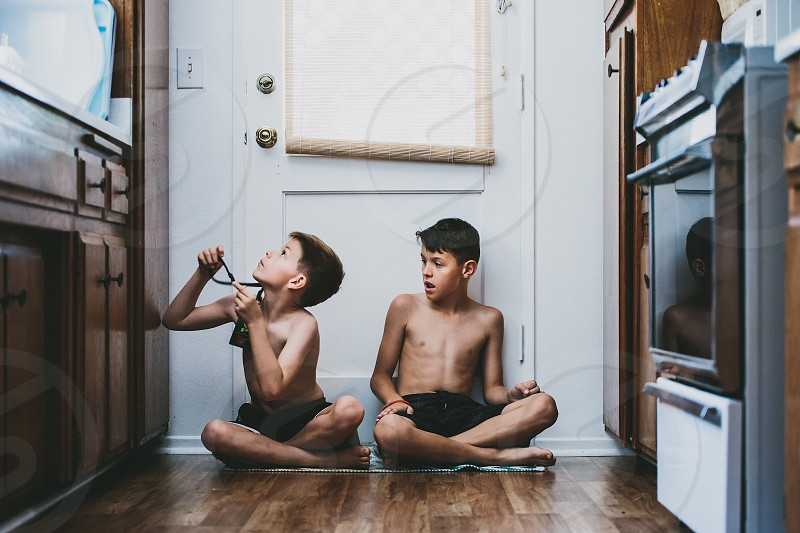 2 boys sitting beside door photo