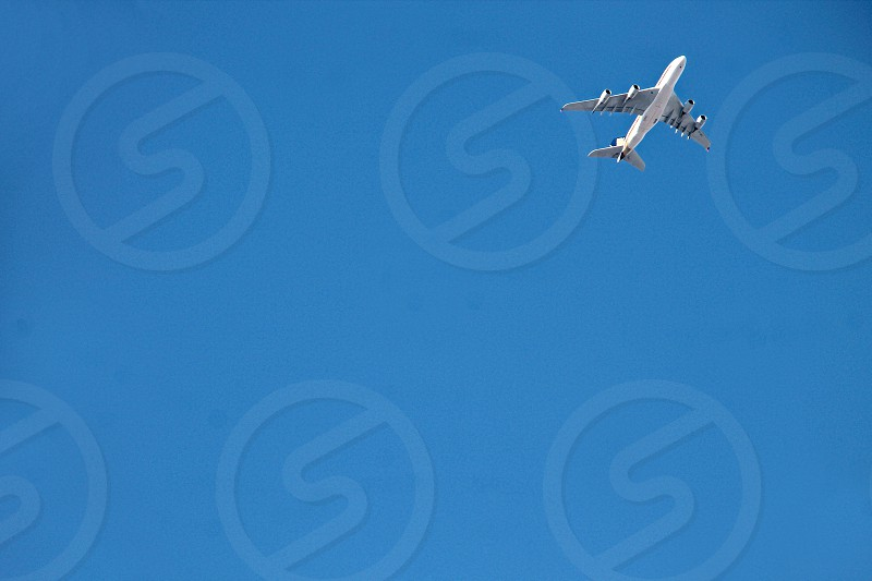 passenger plane flies upward against a clear blue sky photo