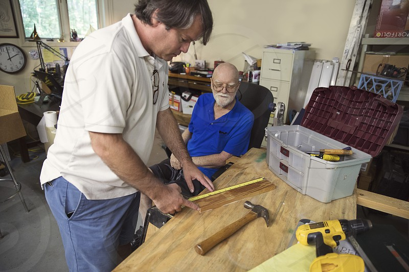 Retired master carpenter teaching student how to build a rocking horse photo
