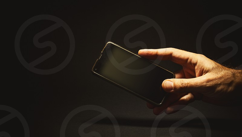 Conceptual composition about communications. Man's hand holding a mobile phone.  photo