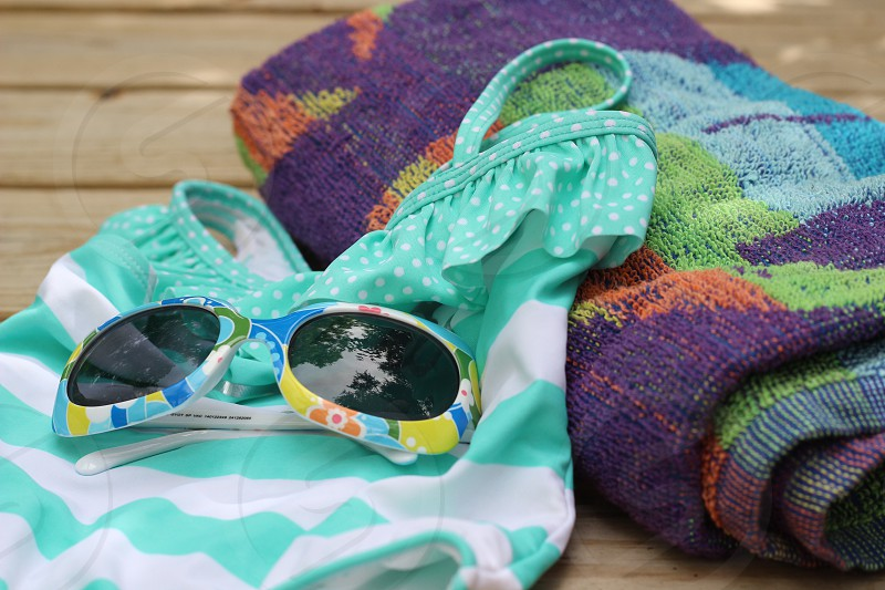 girl's white and teal striped print one piece multicolored sunglasses beside purpleorange and teal towel photo