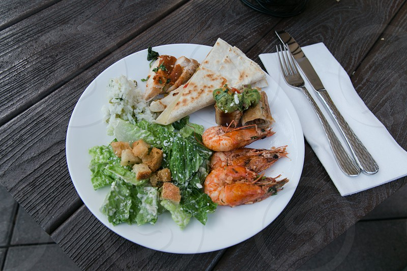 sauteed shrimps beside pizza crust and mash potato and caesar salad as side dish photo