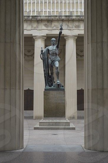 statue of man holding sword and fairy on pedestal photo