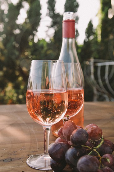 two wine glasses filled with rose wine on a table next to the wine bottle and purple table grapes with trees in the distance photo