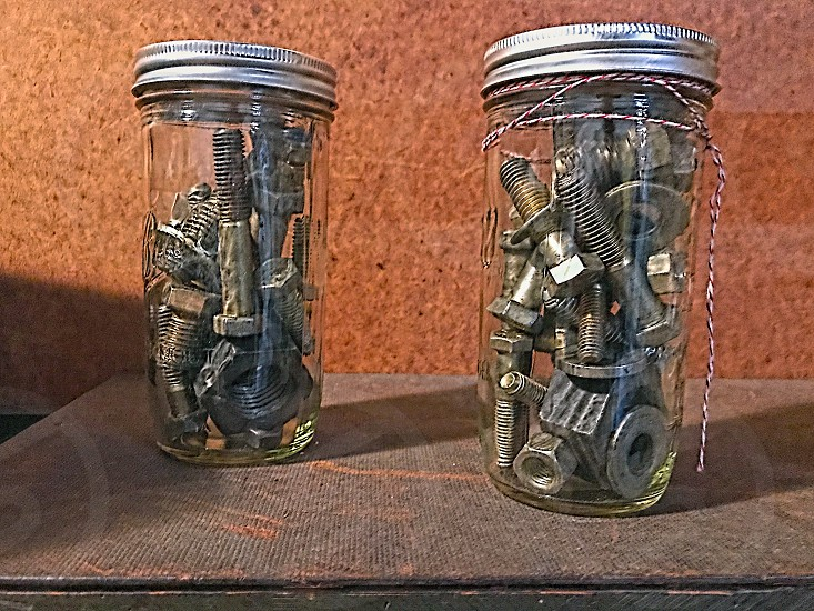 Two glass jars filled with metal nuts and bolts photo