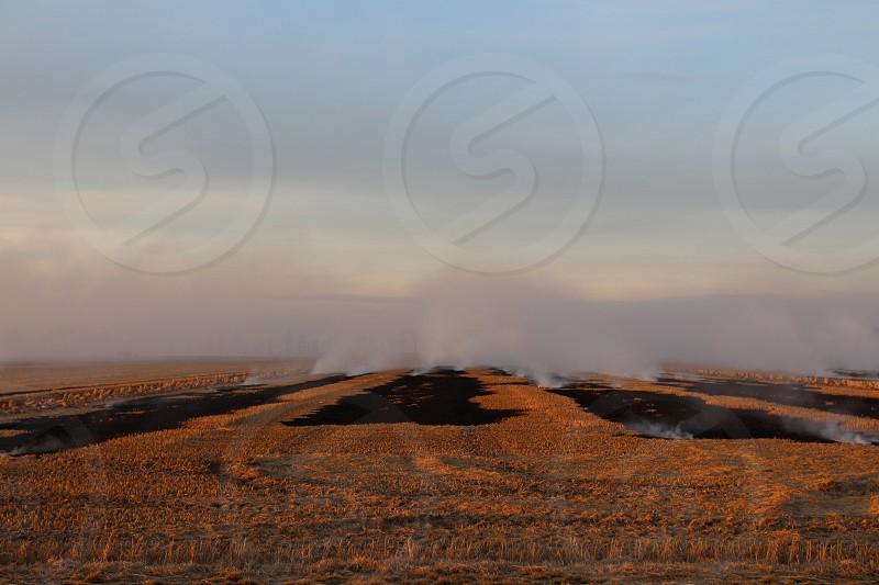 Burning fields with smoke on horizon photo