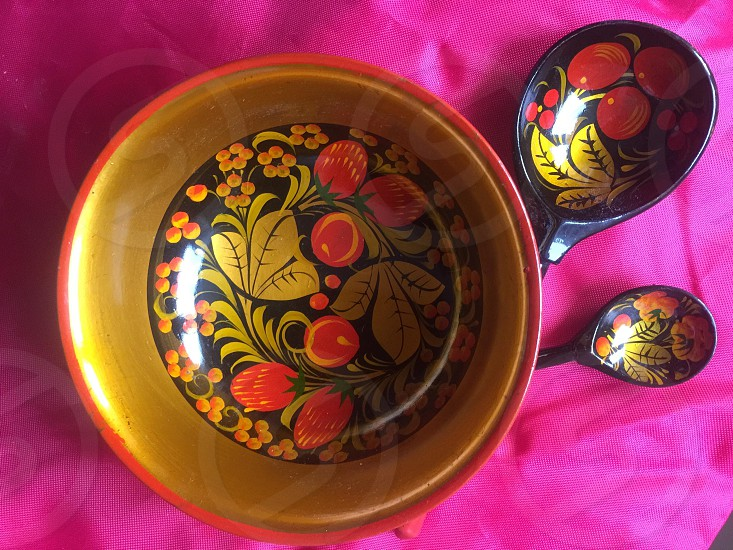 round multicolored floral bowl and ladles on pink textile photo