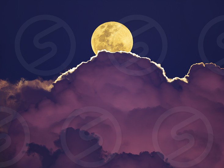 The full moon rises over thunderstorm clouds. High quality image taken through telescope. photo