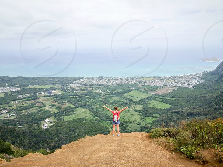 Woman standing on top of a mountain at the edge lookout hands in the air for joy of a beautiful view in Hawaii nature environment lifestyle outdoor  photo