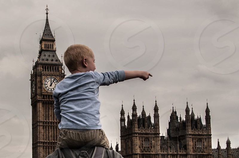boy in light blue on man's shoulders pointing past big ben under grey cloudy sky photo