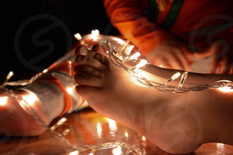 Barefoot kids in Christmas lights photo