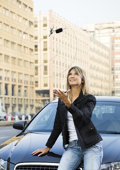 woman; car; keys; smiling; happy; automobile; transportation; Happiness; vertical; outdoors; day; playing; throwing; car keys; looking up; new; portrait; sitting; cheerful; casual clothing; copy space; vehicle; transport; new car; one person; People; female; young adult; young adult woman; young woman; 20s; 20-24 years; 25-29 years; blonde hair; blond hair; caucasian; urban scene; city; street; italy; Milan; attractive; auto; driver; hand; owner; pride; rental; smile; success photo