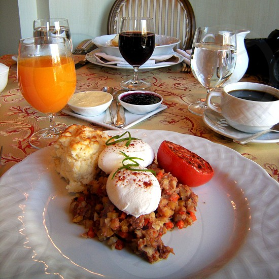 Breakfast table with poached eggs on corned beef hash broiled tomato biscuit butter and jam orange juice coffee and grape juice photo
