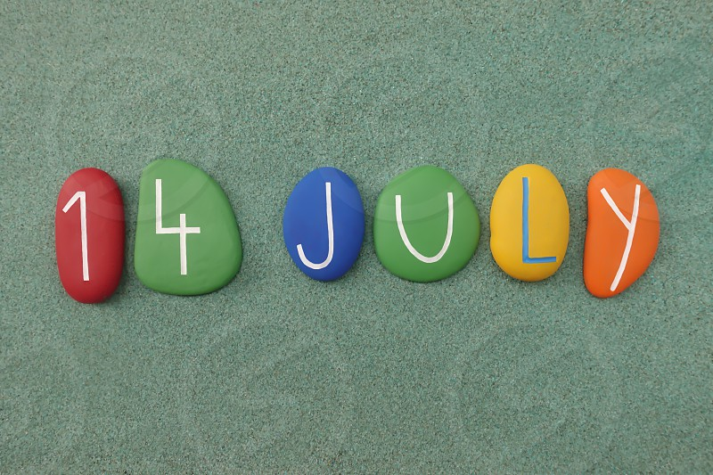 14 July calendar date composed with multi colored stones over green sand                              photo