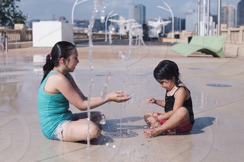 kid wearing gray tank top beside girl wearing black spaghetti strapped top playing water photo