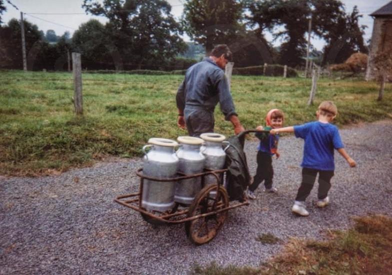 Fresh milk milk urn farmer milking the cows helping children  photo