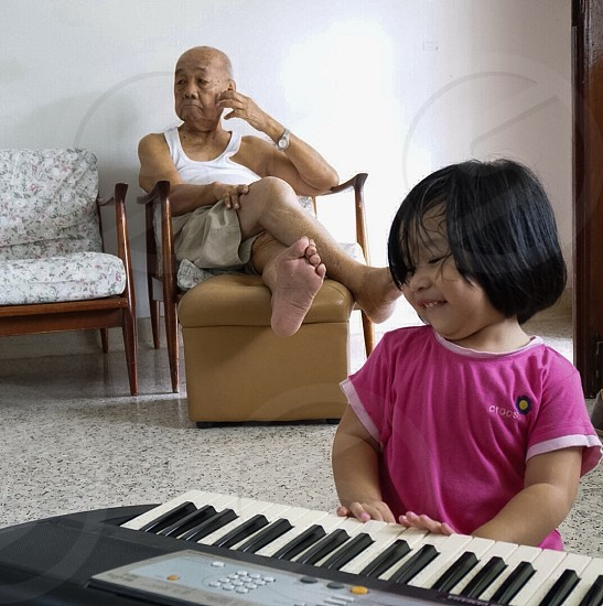 Little girl entertaining her grandfather photo