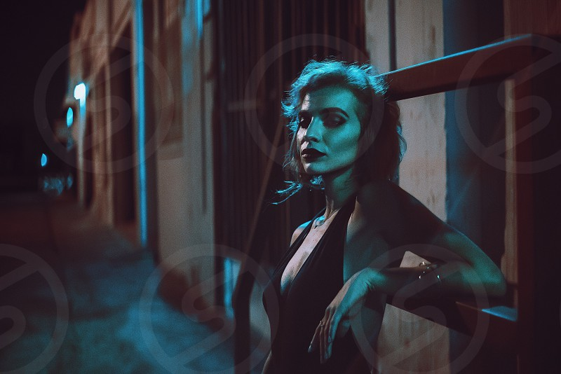 woman in black halter dress standing and leaning on wall during nighttime photo
