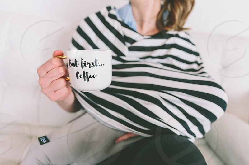 A woman breastfeeding and holding coffee mug. photo