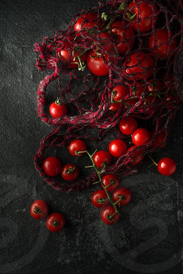 Fresh tomatoes in a string sack on a dark background photo