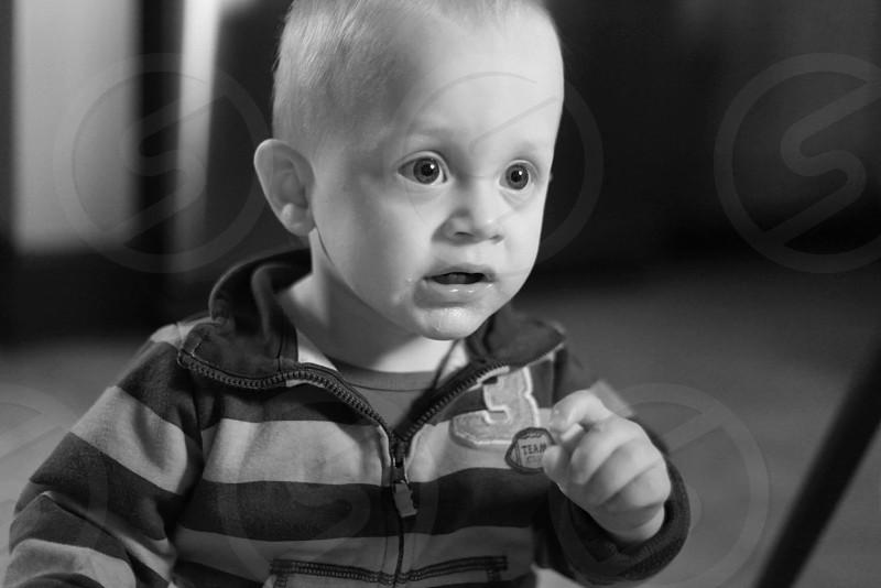 black and white photo of child wearing striped jacket  photo