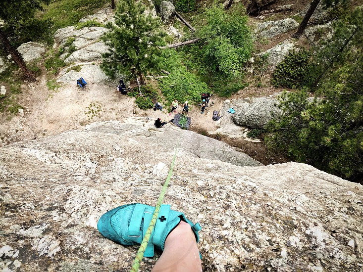 Climber looking down at her belayer climbing party  photo