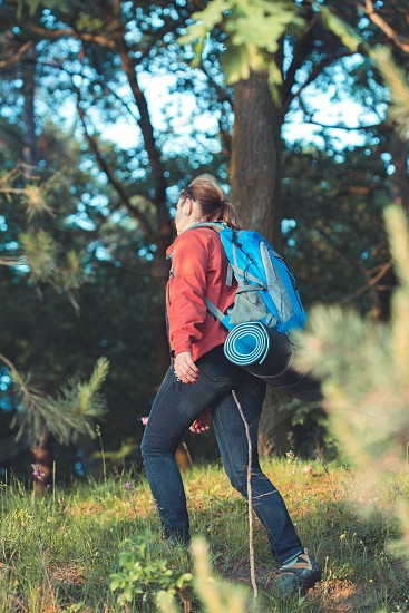 Young woman hiker with backpack walking along the path through the forest during summer vacation trip photo
