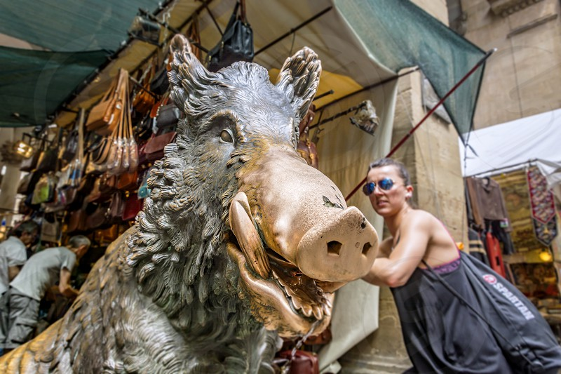 Florence Italy June 2015: close up view of the famous bronze statue of a boar in the Mercato del Porcellino (piglet market) with a tourist and some leather bags vendors in the blurred background photo