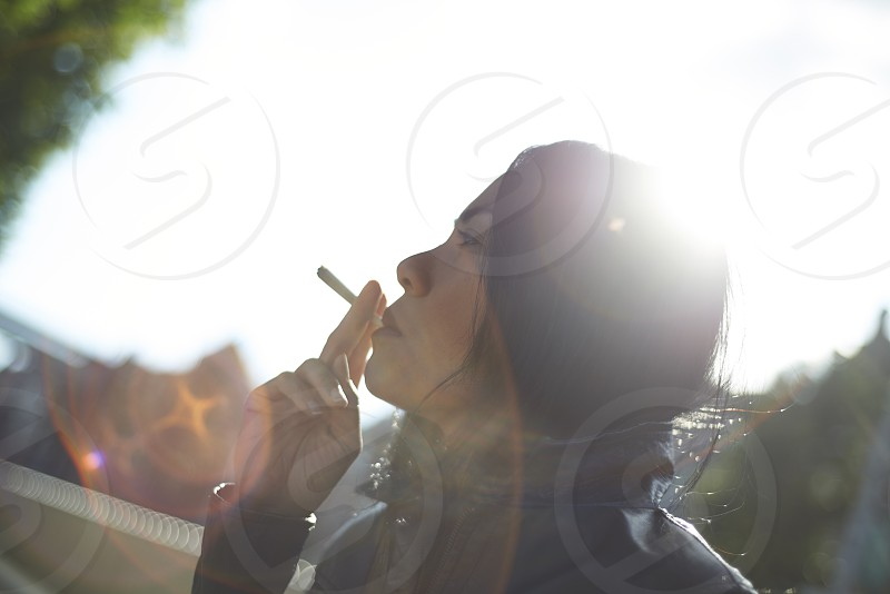 Asian woman taking a pull from a joint enjoying the marijuana photo