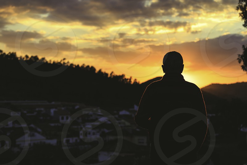 Silhouette of old man with his back to the sunset with sun and mountain on background photo