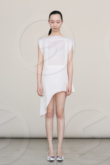 woman wearing white short sleeve dress with sheer panel and asymmetrical hem and white heels standing in front of white wall photo