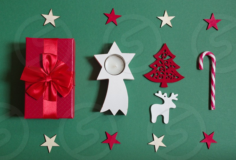 Flat lay of red Christmas gift and Christmas ornaments against the green background photo