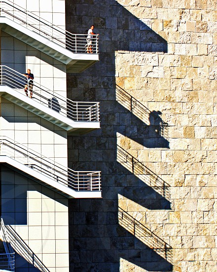 Two people stand on different levels of an exterior staircase whose shadows are thrown on the side of the large building photo