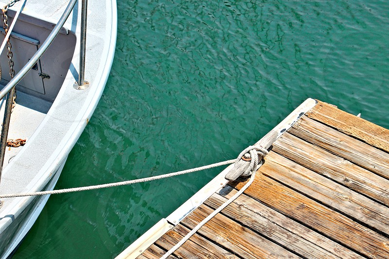 Aerial view of a portion of a rowboat tied to a wooden dock. photo