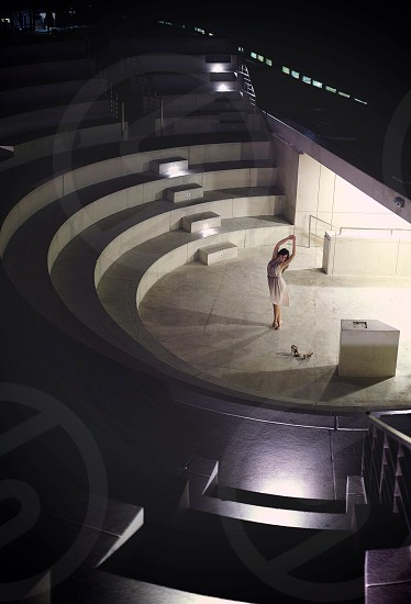 woman in white dress posing on round theater surrounded by stacked seating photo