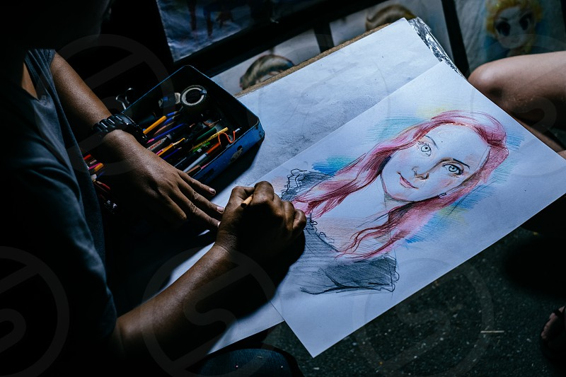 Street Artist is painting a beautiful woman with red hair on the street during night market photo