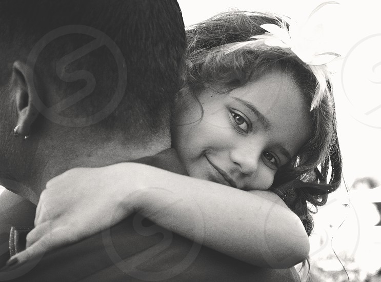 grayscale photo of a girl with a headband hugging a man in polo shirt photo