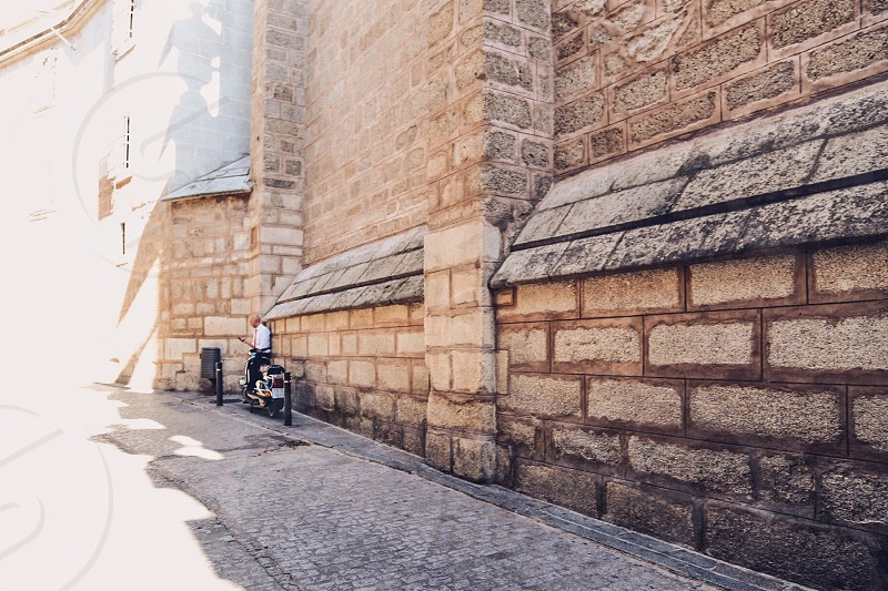 Street photography  man looking at smartphone  Vespa wall stone wall proper man ancient building  photo