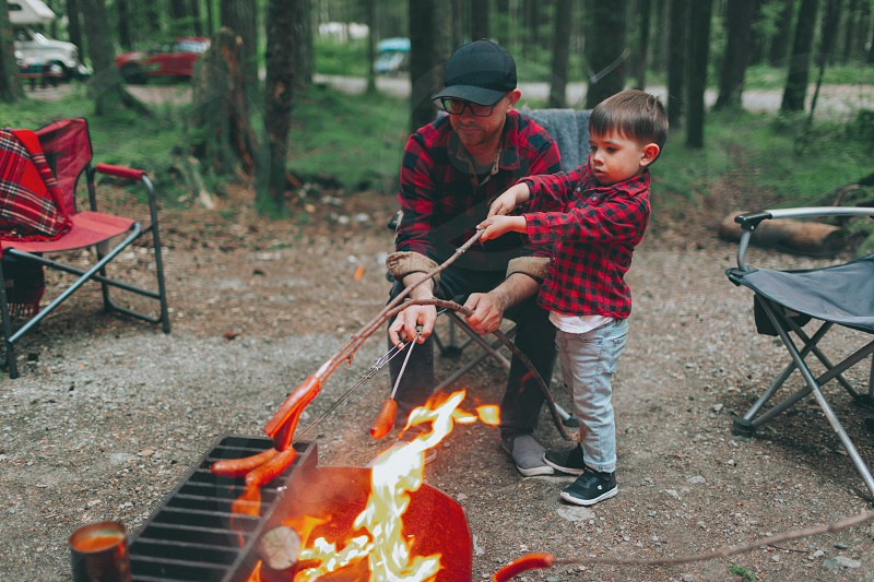 A father and son roasting hot dogs over the fire.  photo