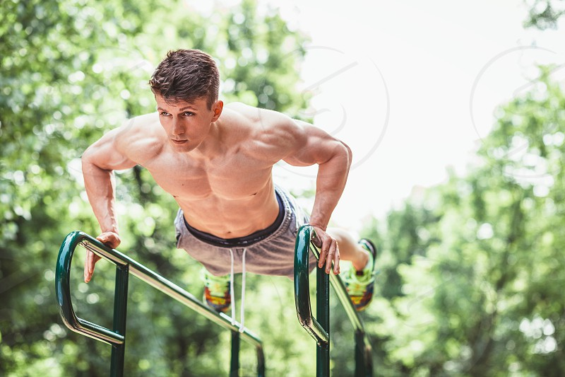 Young fit man doing push ups on bars in an outdoors gym photo