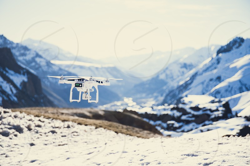 drone flying over mountains. white drone hovering in a bright blue sky. New technology in the aero photo shooting. photo