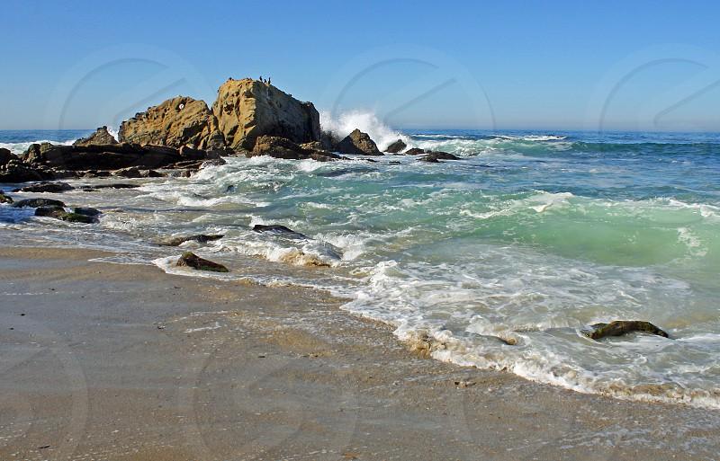 Waves crash on the rocky shore photo