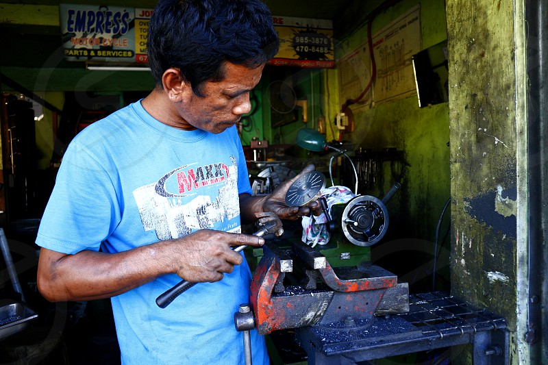 ANTIPOLO CITY PHILIPPINES - MARCH 9 2019: A machine shop worker repairs a motorcycle part for a customer. photo