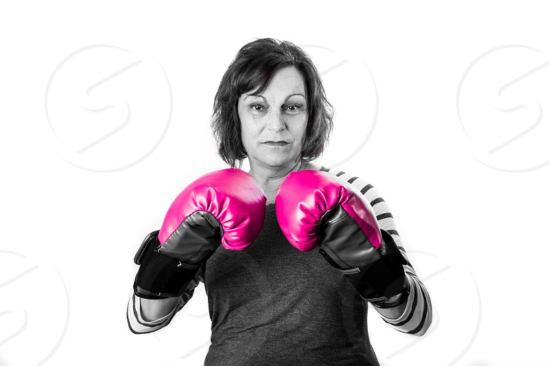 Older woman in pink boxing gloves in a studio setting. Breast cancer awareness. photo