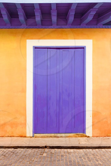 Purple door surrounded by an orange wall in a town in Cuba photo
