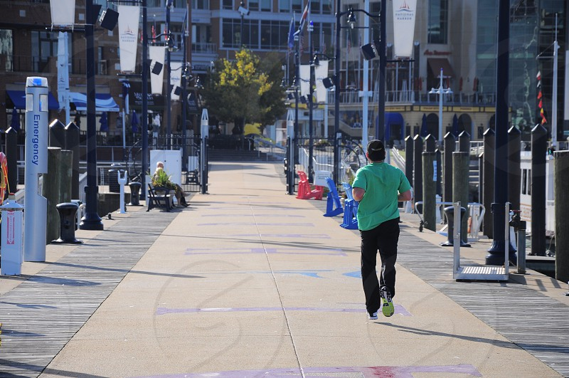 man in green shirt and black pants jogging at the street photo