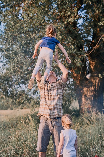 Father tossing little girl in the air. Family spending time together on a meadow close to nature. Parents and children playing together. Candid people real moments authentic situations photo