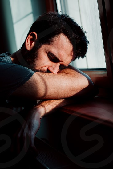 Bearded young man by the window in despair  photo