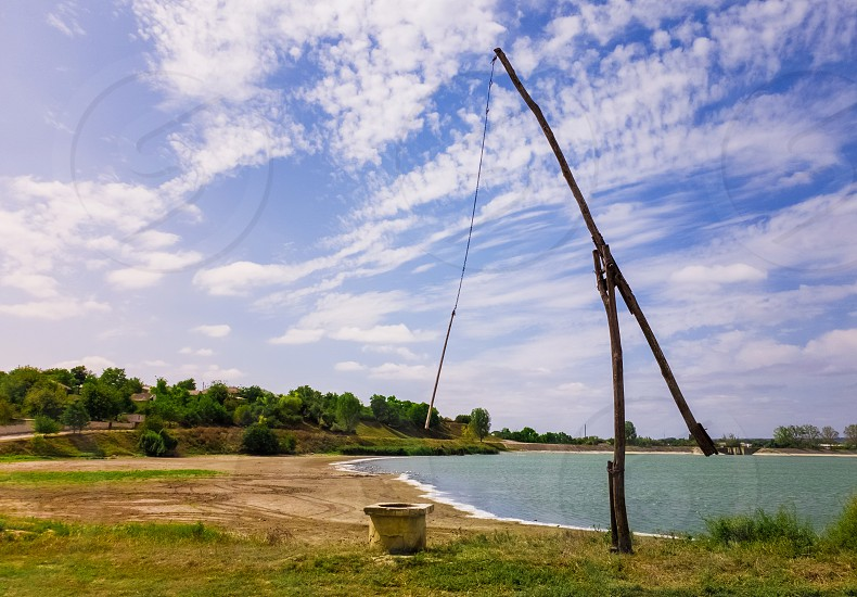 Idyllic countryside scene with an old water well sweep (shadoof) near the Delia lake (Moldova). Also called a counterpoise lift or well pole is an ancient irrigation tool and used for watering crops. photo